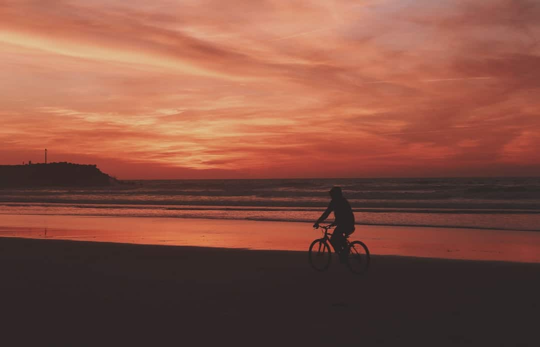 A person riding a horse on a beach with a sunset in the background