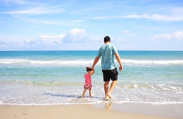 A man and a kid standing next to the ocean