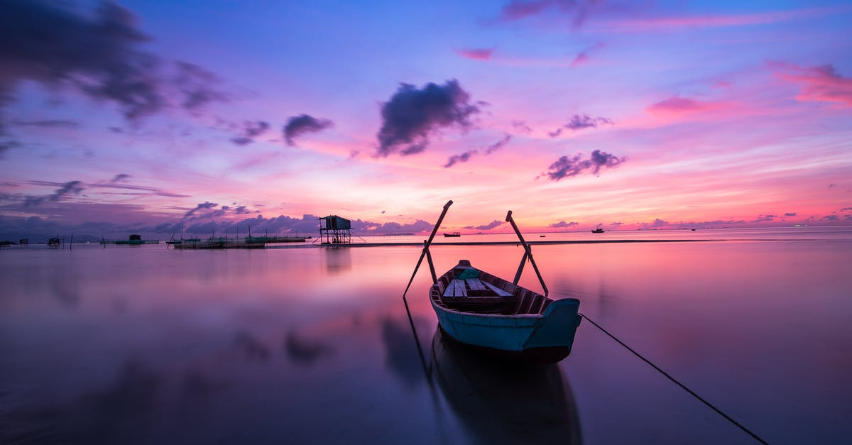 A small boat in a body of water with a sunset in the background